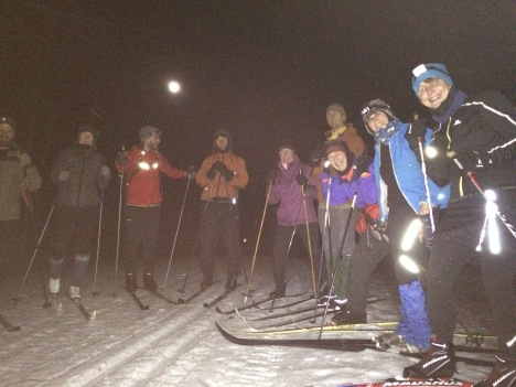 Skiers under the bright full moon.